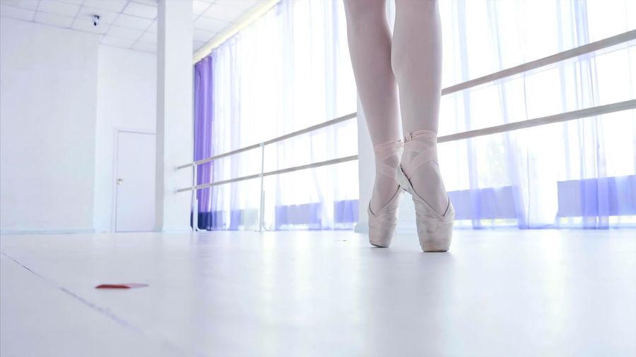 Low section of ballet dancing on floor