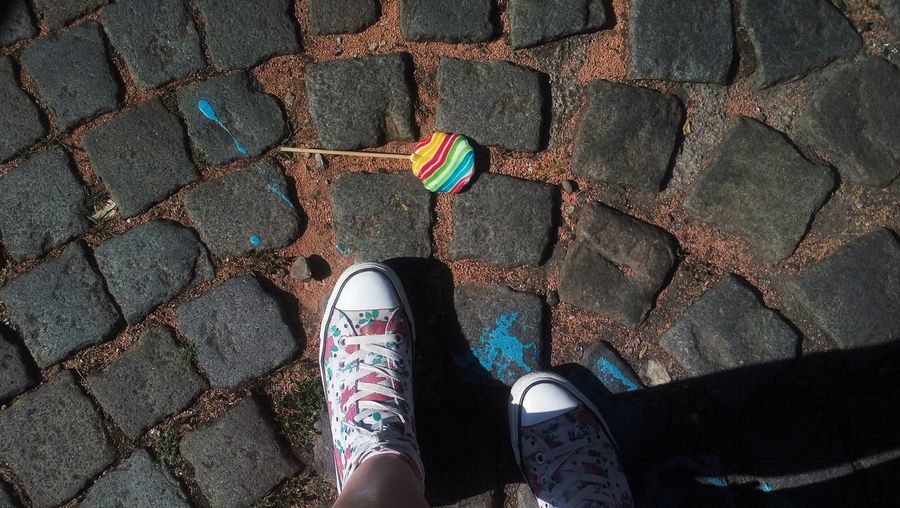 Low section of person standing by multi colored shoes