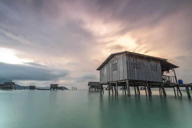 Stilt House By Sea Against Sky During Sunset