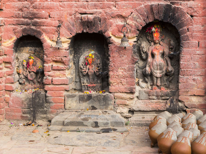 Clay pots drying next to three different-sized niches with old carved hindu deities covered in red powder and floral offerings, Potter's Square, Bhaktapur, Nepal Bhaktapur,Nepal Clay Pots Potter's Square Medieval City Craft Hindu Deities Red Powder Floral Offering Old Carved Statues In Niches Drying Pink Brick Brick Three Place Of Worship Spirituality Religion Sculpture Statue Art And Craft