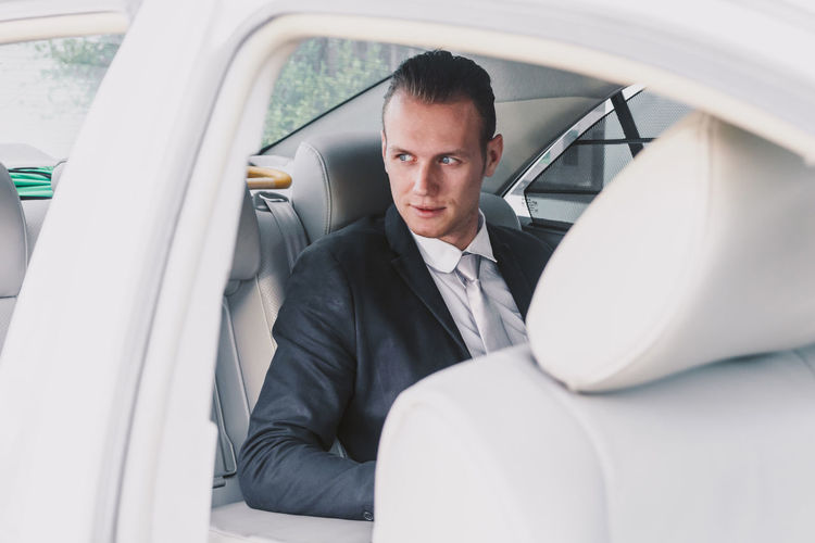 Businessman looking away while sitting in car