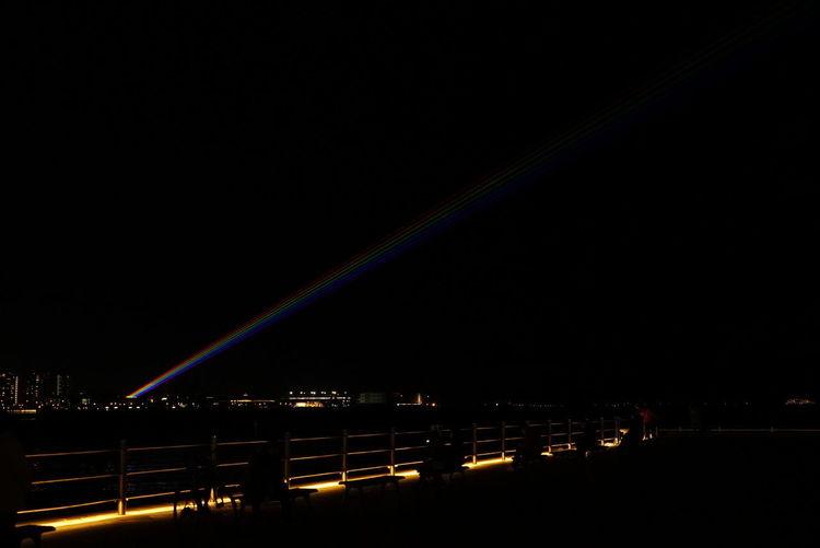 Rainbow over illuminated city against sky at night