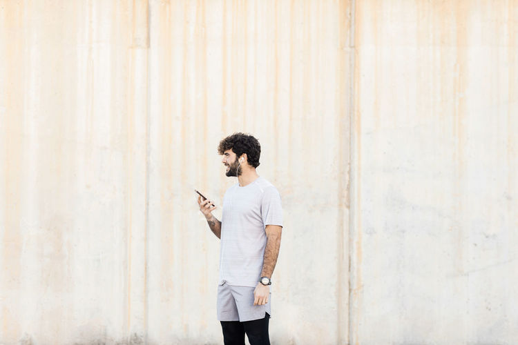 Full length of young man using phone while standing against wall