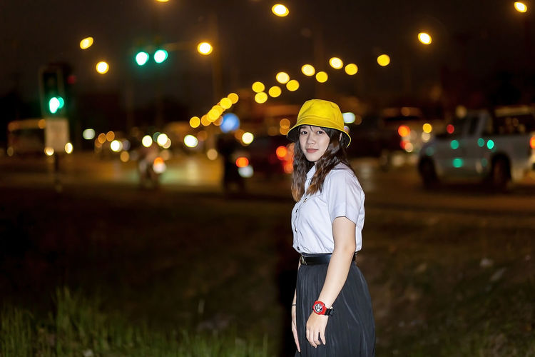 Woman standing by illuminated lights at night