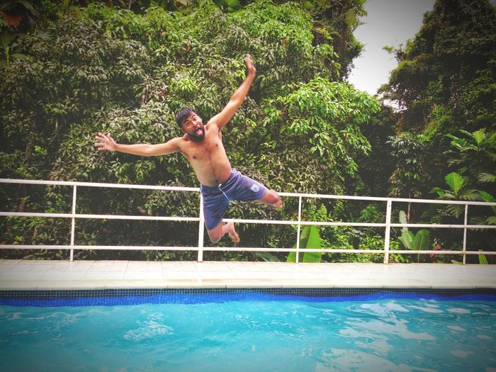 Mid adult man diving into swimming pool