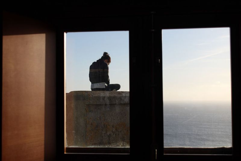 Man standing by window against sea
