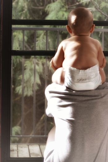 Rear View Of Father Carrying Shirtless Toddler On Shoulders By Window At Home