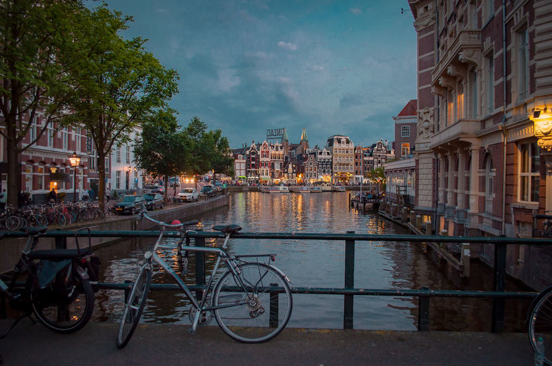 Bicycle by canal against buildings in city