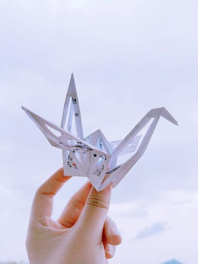 Cropped hand holding origami against cloudy sky