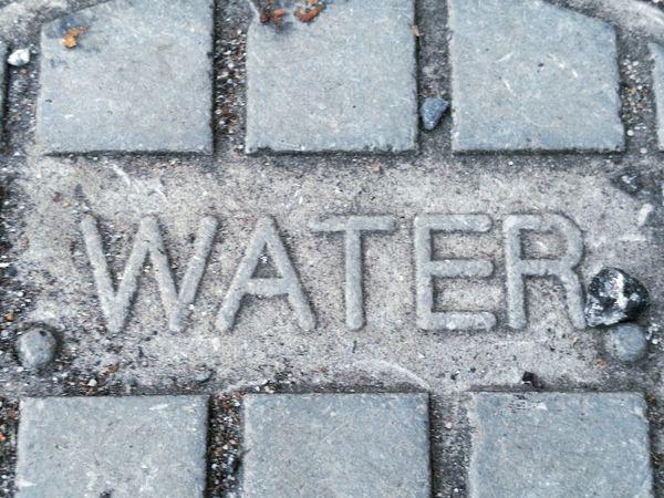 Outdoors No People Full Frame Alphabet Western Script Water Word Letters Floor Utility Grey Overhead