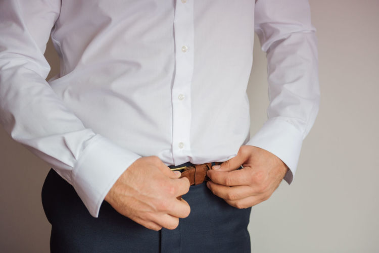 Midsection Of Businessman Wearing Belt Over White Background