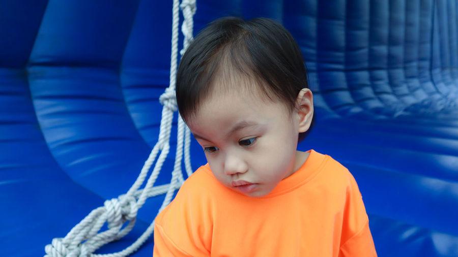 Cute boy sitting on play equipment