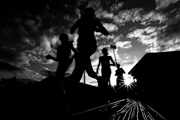 Low angle view of silhouette people against cloudy sky