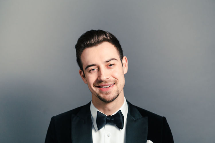 Portrait of happy young man wearing tuxedo against gray background