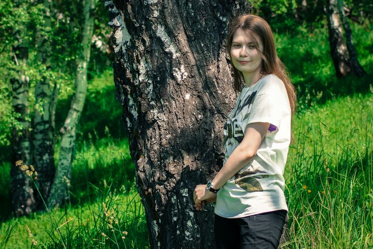 Woman standing by tree on grassy field