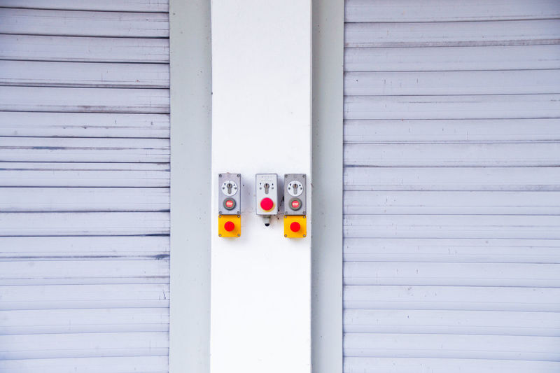 Push buttons on wall amidst closed shutters