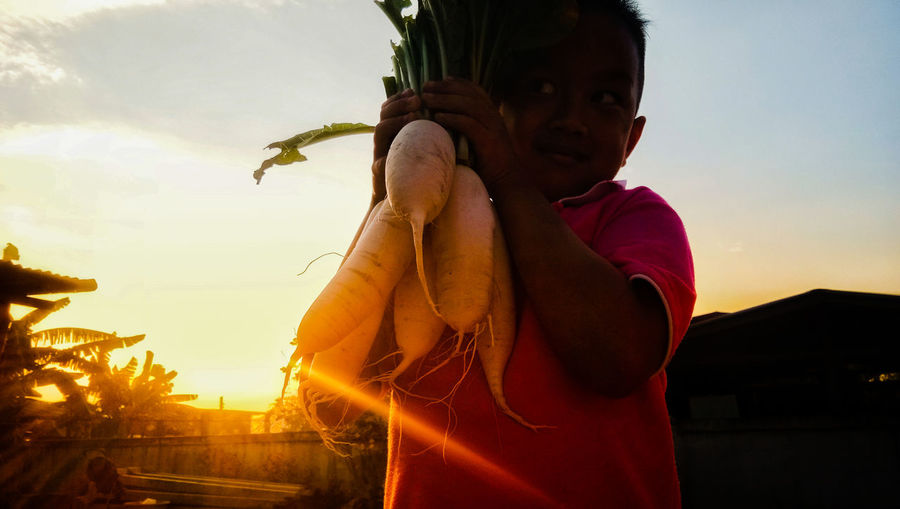 Low angle view of boy holding radish while standing against sky during sunset