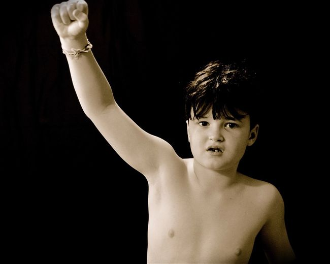 Portrait of shirtless boy against black background