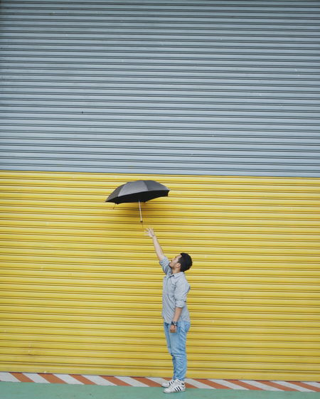 Side view of man with umbrella standing by closed shutter