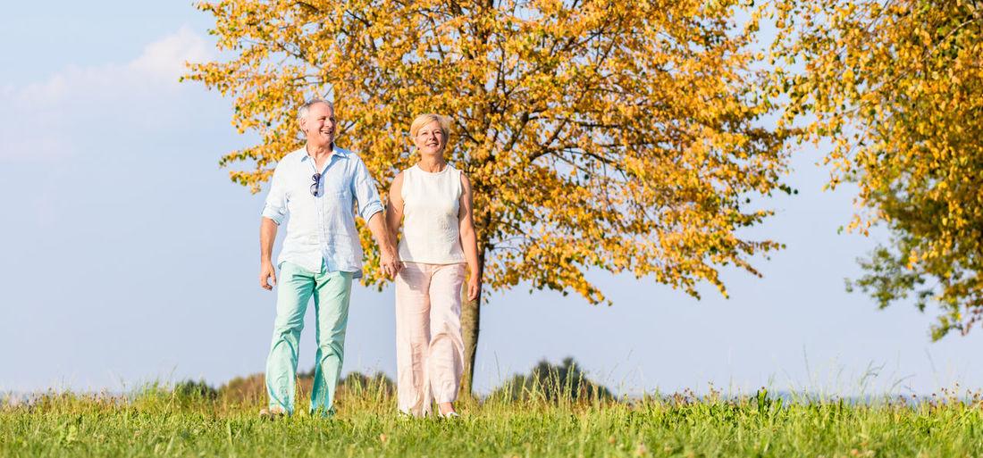 Full length of couple walking on land against sky