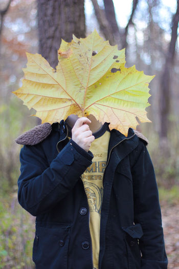 Man holding leaf in front of face