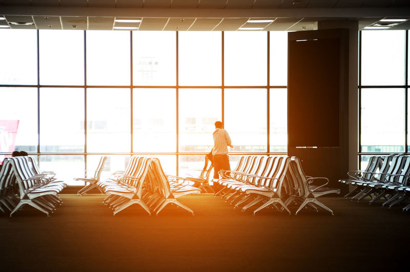 Man Standing By Seats At Airport Terminal