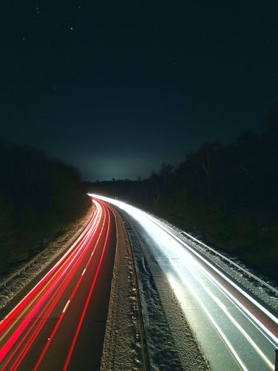 Light trails on highway against sky at night