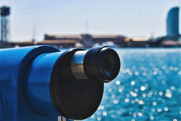 Close-up of coin-operated binoculars by sea against clear blue sky