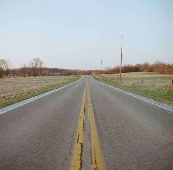 Pale blue sky and over a grey country road between two fields in the spring in Indianapolis, Indiana. Asphalt Country Road Day Diminishing Perspective Empty Empty Road Film Indiana Landscape Long MidWest Nature No People Non-urban Scene Outdoors Road Road Marking Sky Spring Surface Level The Way Forward Tranquil Scene Tranquility Transportation Vanishing Point