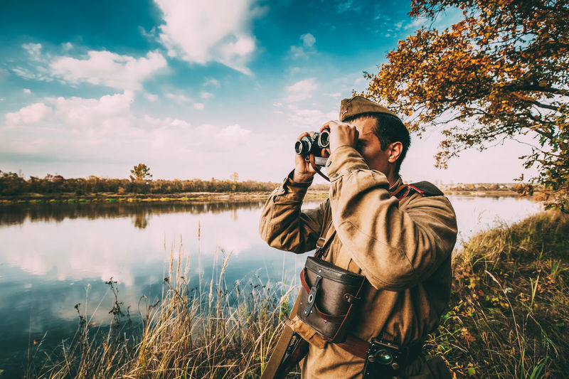 Man photographing by lake against sky