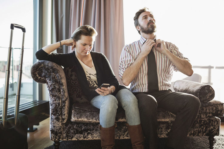 Full length of young couple sitting on sofa