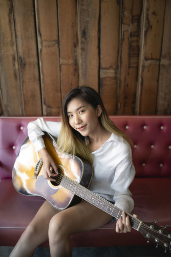 Portrait of smiling young woman playing guitar while sitting on sofa