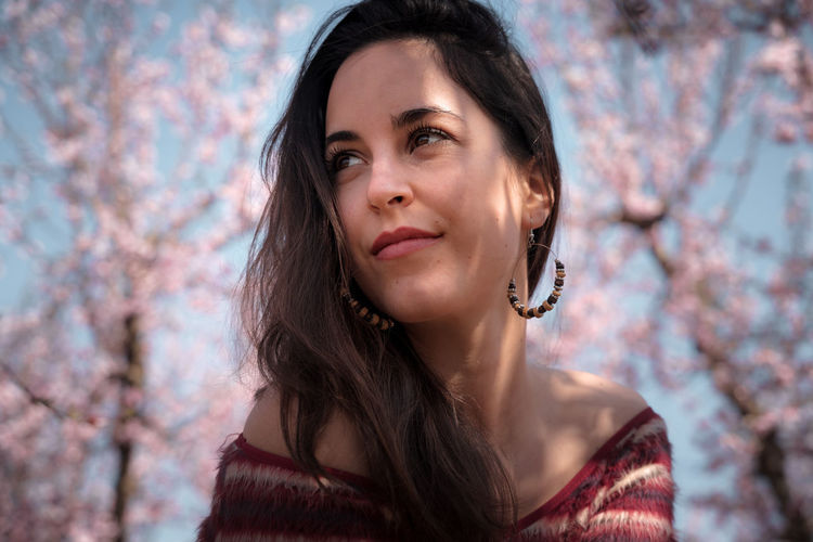Portrait of a beautiful young woman against cherry blossoms