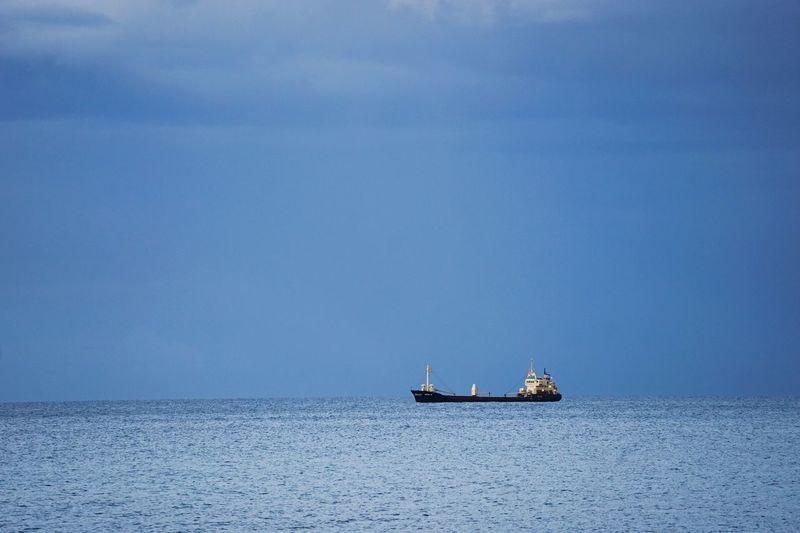 Boat sailing on sea against blue sky