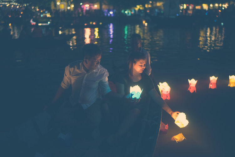 High angle view of people holding illuminated candles while sitting in boat on river at night