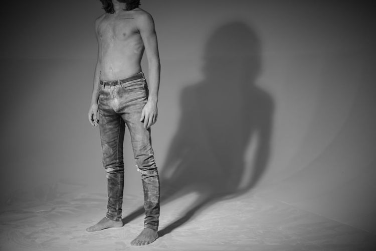 Low Section Of Shirtless Man While Standing Over White Background