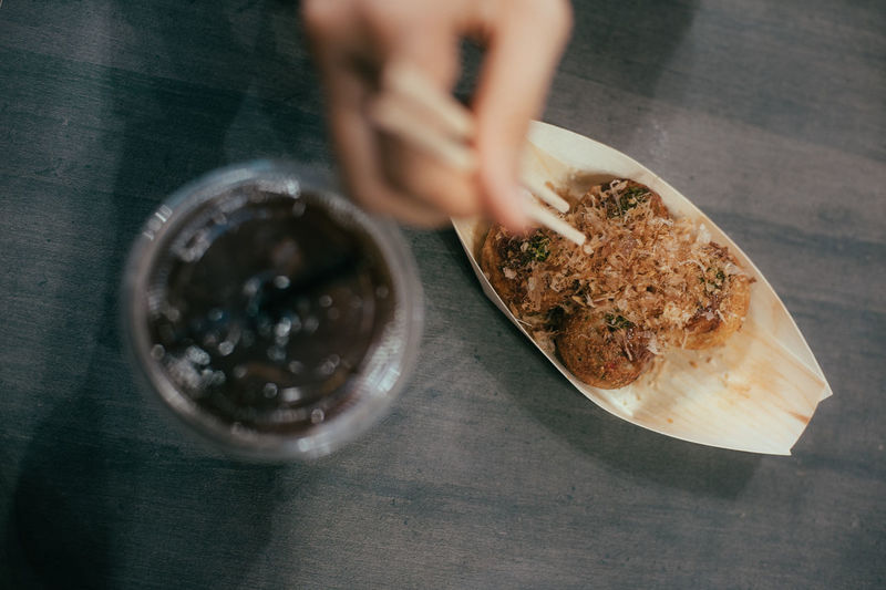 Cropped hands eating takoyaki using chopsticks on table