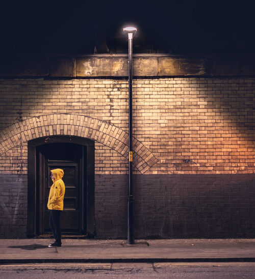 Full length of man standing against wall at night