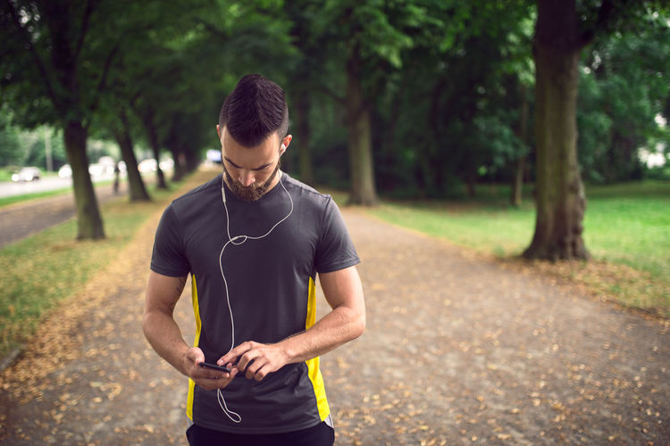 Athlete listening to music through mobile phone in park