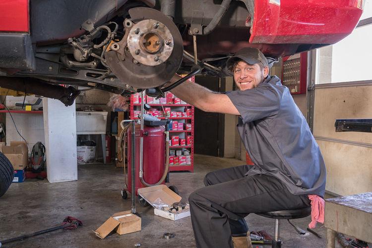 Car Mechanic replacing brakes Auto Mechanic Axel Break Car Car Lift Cars Caucasian Fix  Indoors  Looking At Camera Male Mechanic Mechanical Repair Shop Shop Smile