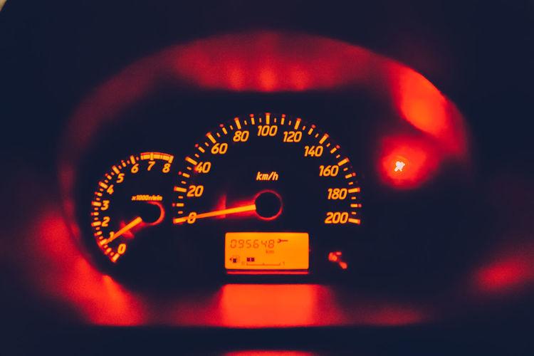 Close-up of illuminated red speedometer in car