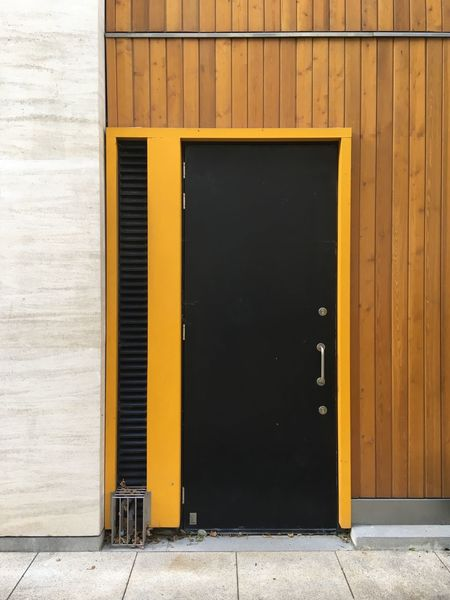Black door with yellow frame on wooden wall Black Door Door Door Frame Doorframe Yellow Frame EyeEm Selects Yellow Built Structure Architecture Building Exterior Closed Wall - Building Feature Door No People Entrance Security City Safety Day Wood - Material Protection Building Street