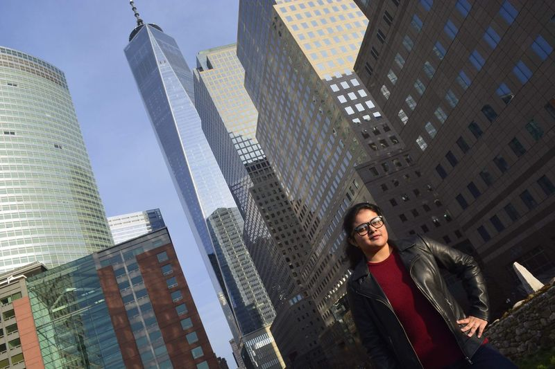 Low angle portrait of young woman standing against one world trade center