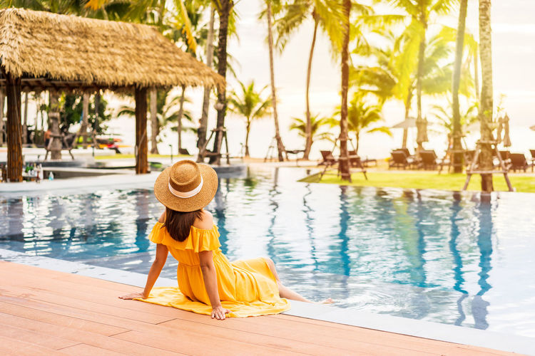 Woman relaxing in swimming pool against palm trees