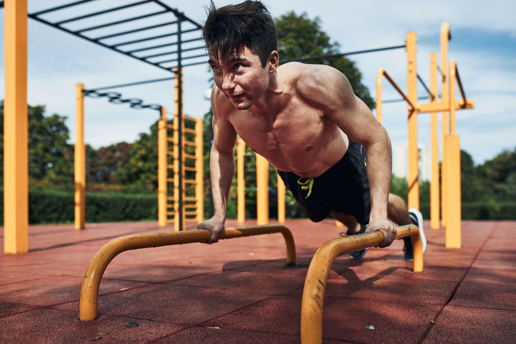 Full length of shirtless young man exercising at playground
