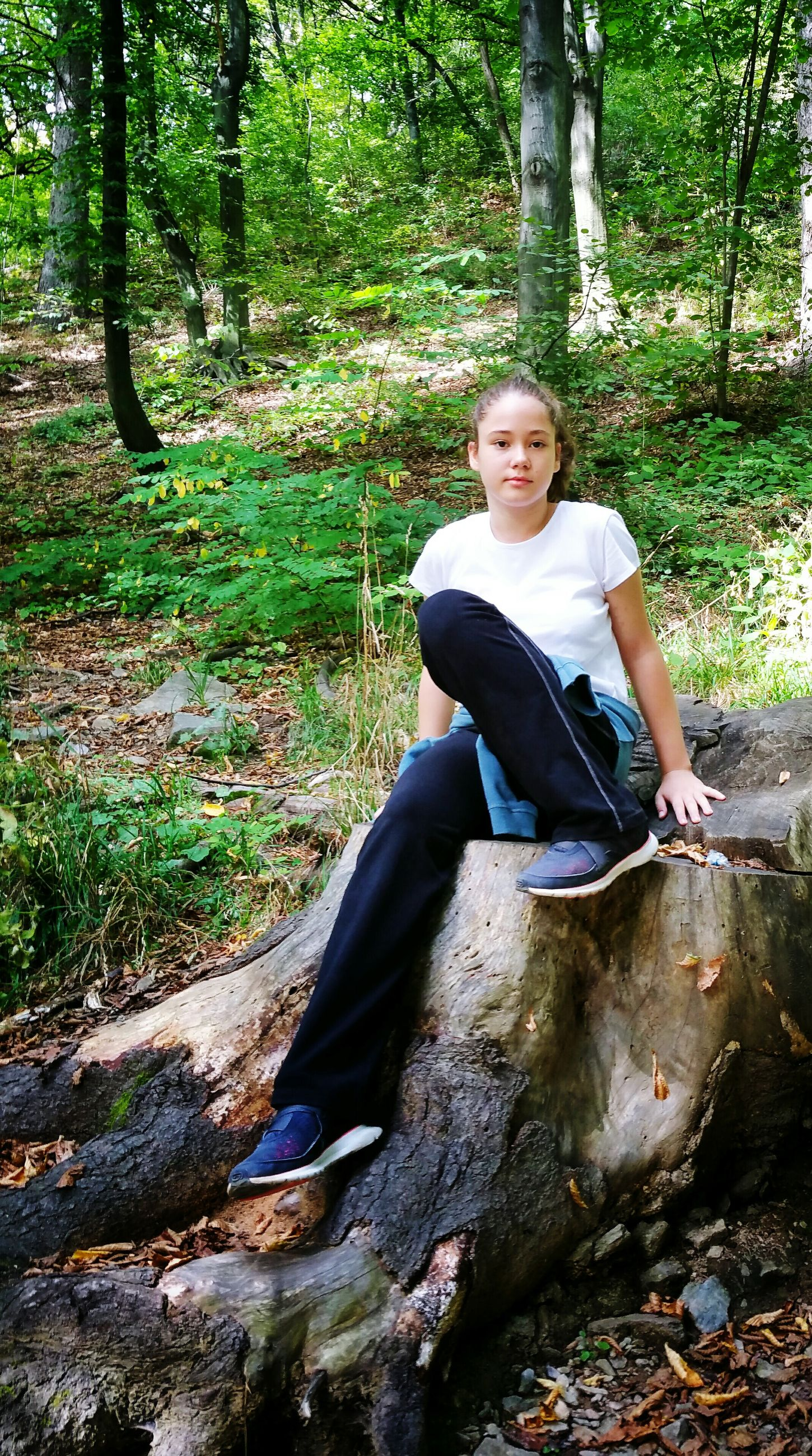 full length, tree, sitting, casual clothing, one person, looking at camera, front view, real people, leisure activity, childhood, portrait, lifestyles, outdoors, day, smiling, people, nature, young adult, adult