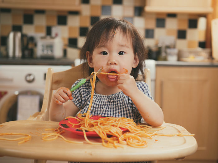 baby girl eating messy spaghetti Messy Asian Baby Girl Baby Girl Childhood Close-up Cute Day Domestic Kitchen Food Food And Drink Freshness Front View Home Interior Indoors  Italian Food Looking At Camera One Person People Plate Portrait Real People Table
