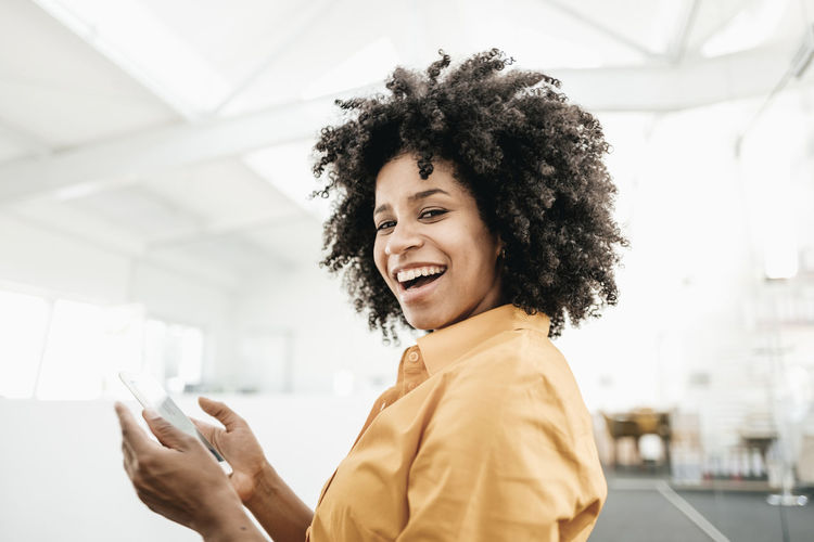 Portrait of a smiling young woman using phone