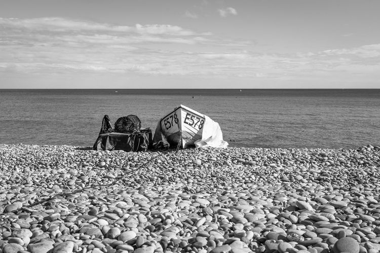 Lounge chairs and pebbles on beach against sky