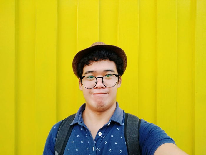 Portrait Of Young Man Wearing Eyeglasses Against Yellow All